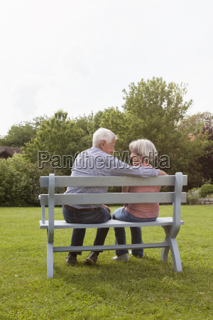 happy senior couple sitting on bench