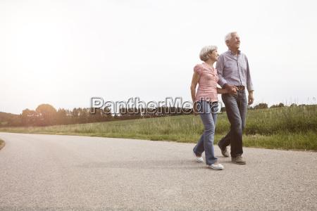 smiling senior couple walking on country
