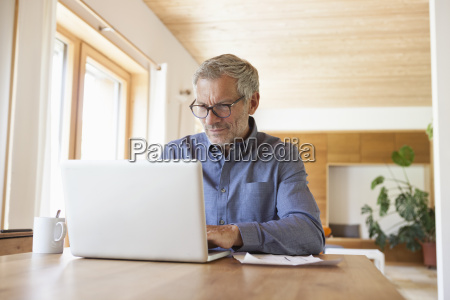 mature man using laptop on table