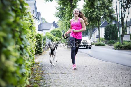 young woman jogging with dog