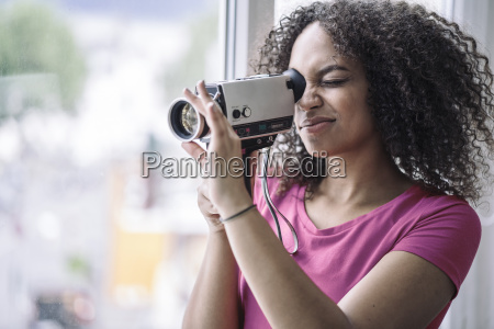 young woman using old school camera