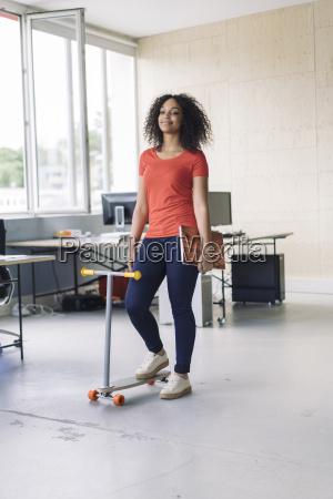 young woman carrying laptop using kickboard
