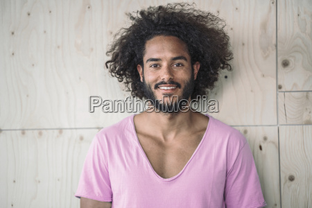young man leaning against wooden wall