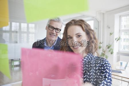 businessman and woman looking at adhesive