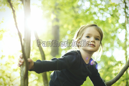 girl in forest climbing in tree