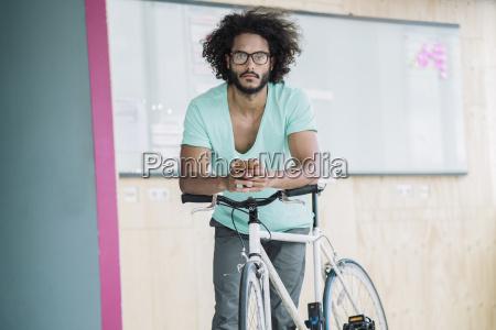 junger mann auf fahrrad lehnen mit