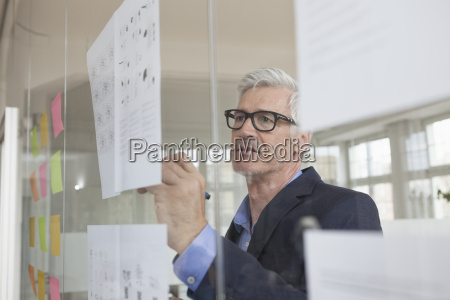 businessman in office writing on paper