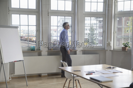 mature businessman standing in office looking