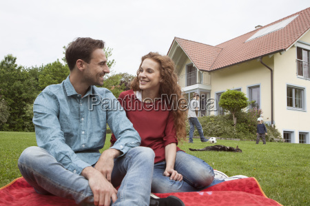 smiling couple in garden with kids