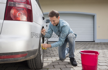 man cleaning car on driveway of