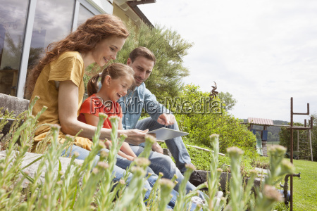 happy family sitting in garden using