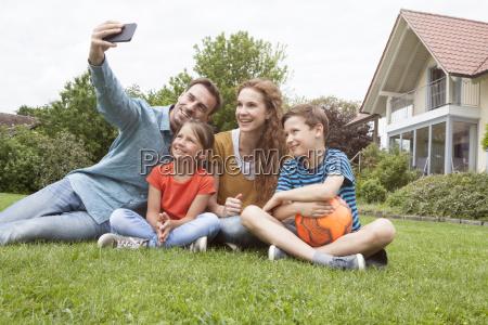 smiling family sitting in garden taking