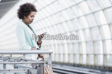 young woman with earphones looking at