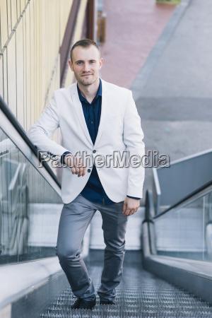 portrait of businessman standing on escalator