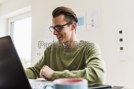smiling man at desk with laptop