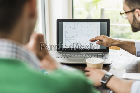 two businessmen analysing line graphs on