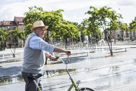 smiling senior man with folding bicycle