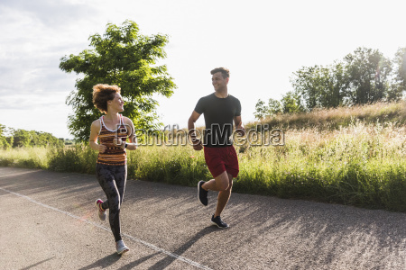 young couple running on country road