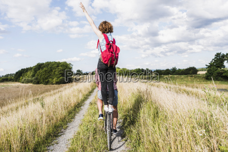 young woman standing on bicycle rack