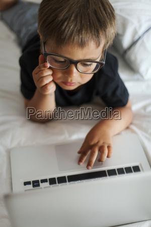 little boy wearing glasses lying on