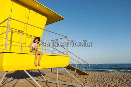 little girl sitting on a yellow