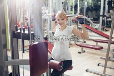 schwangere frau macht UEbungen im fitnessstudio