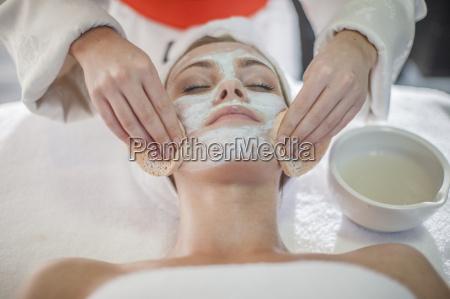young woman in spa receiving facial