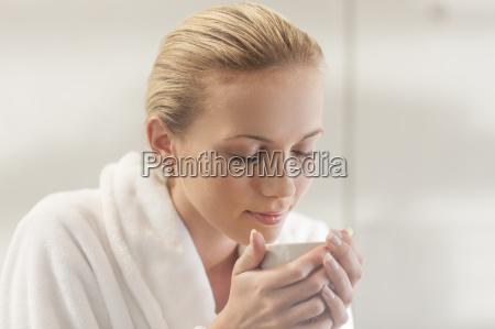 young woman in bathrobe drinking tea