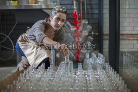 young woman sorting glass bottles