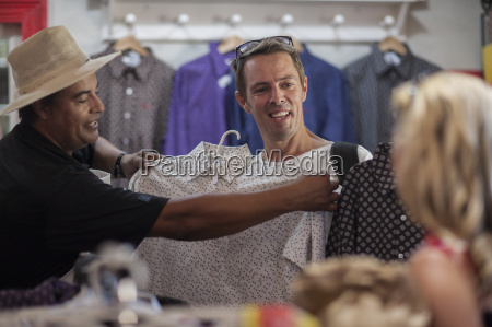 shopkeeper in shop helping clients