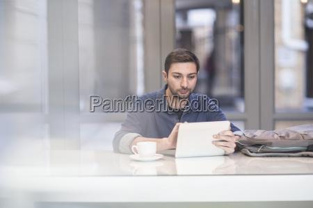 mann mit digitalen tablette am schreibtisch