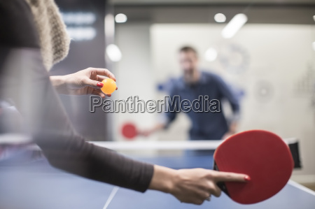 two colleagues playing table tennis in