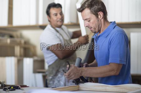 zwei maenner arbeiten in leinwand werkstatt