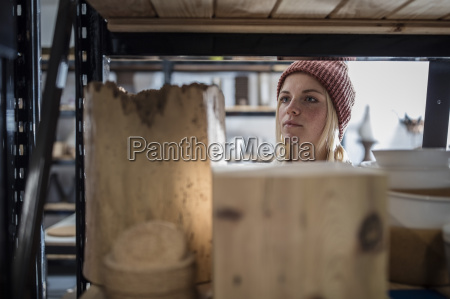 young woman in workshop looking at