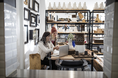 two women with laptop in shop