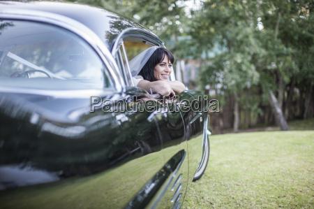 laechelnde braut die im weinleseauto sitzt