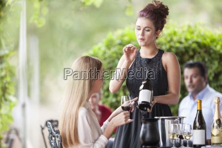 waitress showing wine bottle to woman