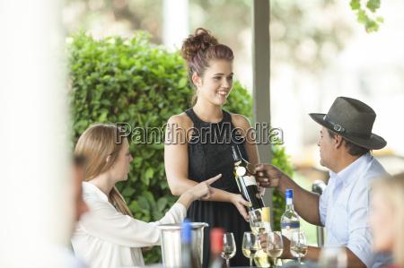 waitress in restaurant showing wine bottle