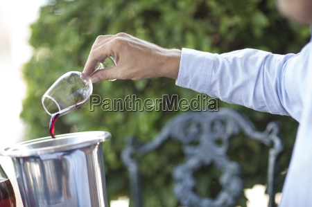 man pouring out glass of red
