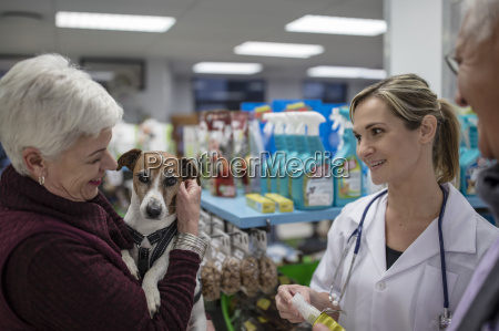 senior woman with dog in shop