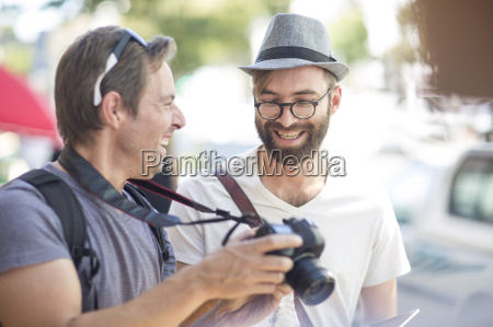 two happy men with camera outdoors