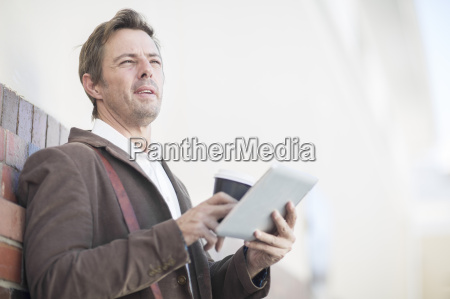 man with digital tablet and coffee