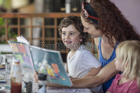 mother reading book to kids