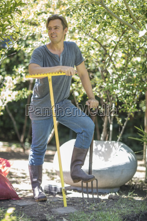 smiling man with gardening tools in