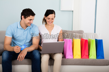 happy couple shopping online with credit