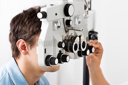 ein optometriker der phoropter fuer patienten