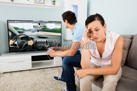 woman sitting beside a man addicted