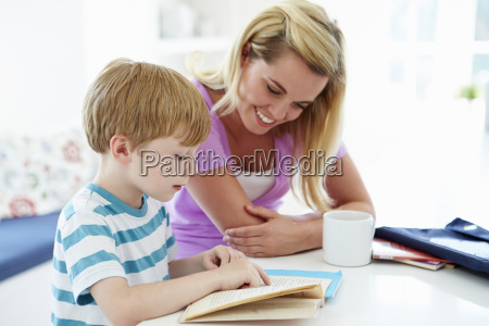 mother helping son with homework in