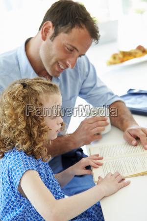 father helping daughter with homework in