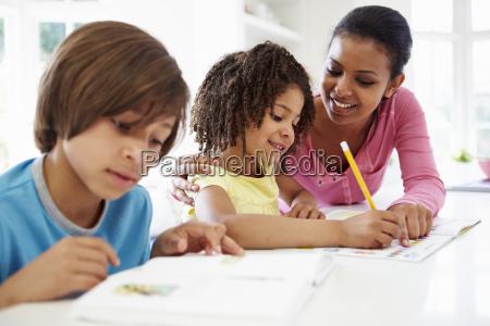 mutter helfen kindern bei den hausaufgaben